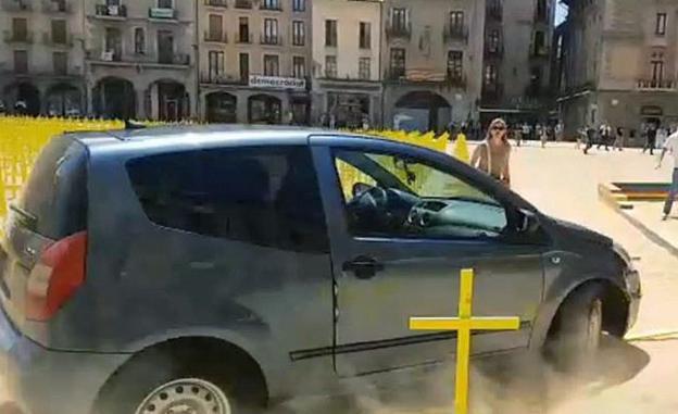 Un coche arrolla cruces amarillas por los políticos presos en la plaza de Vich.