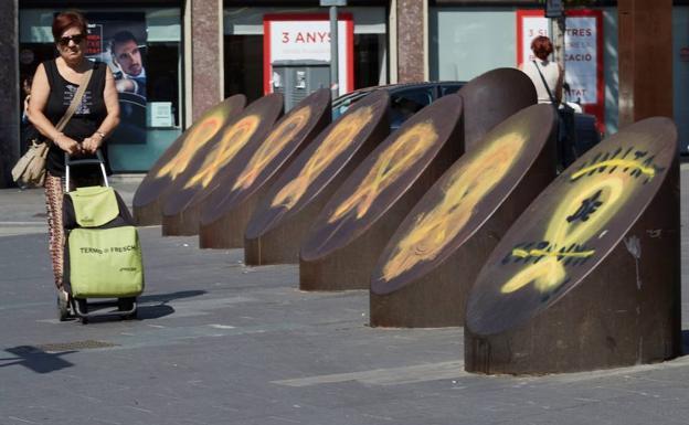 Una mujer pasa ante unos lazos amarillos en el barrio de Sants de Barcelona. /Alejandro García (Efe)